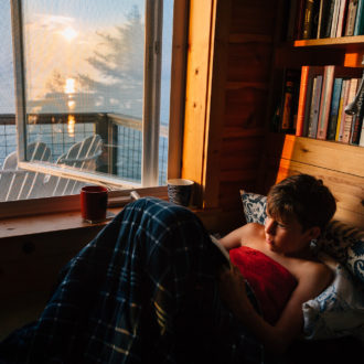 Boy reads book near window at lake house